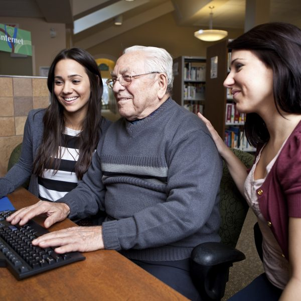 Volunteers teaching a senior how to use a computer employee engagement realized worth
